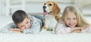 Kids and dog laying on a clean carpet